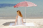 Woman sitting under a beach umbrella on the beach