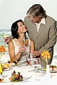 Couple with wine glasses at laid table by sea