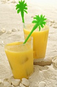 Two glasses of orange juice in sand
