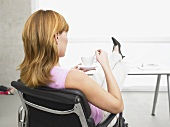 Businesswoman with her feet up on her desk drinking coffee