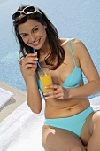 Woman in bikini drinking orange juice by swimming pool