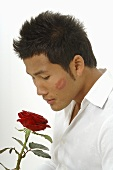 Asian man with red rose and lipstick on cheek