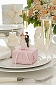 Wedding place-setting: gift, bride & groom figures, glass of wine