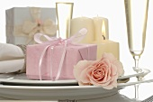Place-setting with pink gift, glasses of sparkling wine