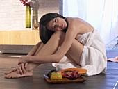 Woman sitting on the floor with papaya and skin care cream