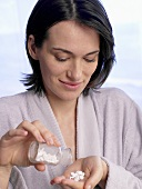 Woman with a small bottle of Schüssler Salts tablets
