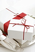 Gifts in white wrapping paper with red bows on silver plate