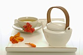 Bowl of tea and teapot on tray