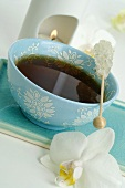 Cup of tea with sugar swizzle stick, aroma lamp, orchid
