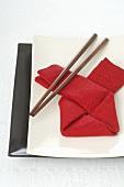 Asiatisches Gedeck mit roter Serviette und Essstäbchen