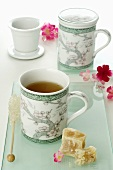 Tea in two Asian mugs, rock sugar, flowers