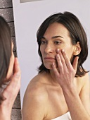 Woman putting cream on her face in front of mirror