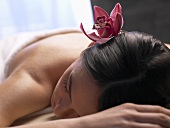 Woman with orchid in her hair on a massage couch
