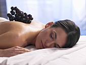 Woman lying on a massage couch with red grapes