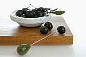 Black olives in small dish and on cocktail stick