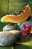 Wedge of papaya on stones