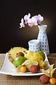 Exotischer Früchteteller und Vase mit Orchideenblüte
