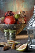 Pomegranates, figs and dates in wooden bowl, lantern