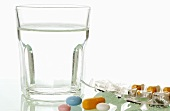Glass of water and various tablets