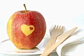 Red apple with heart on plate with wooden knife and fork