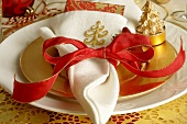 Christmas place-setting with white napkin and red bow