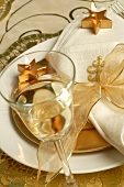 Christmas place-setting with napkin, gold bow, glass of wine