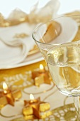 Christmas table in gold with star-shaped candles & glass of wine