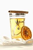Glass of tea with cinnamon stick and slice of orange