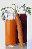Gemüsesäfte in Flaschen und eine frische Möhre