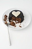 Small chocolate cake with heart, partly eaten