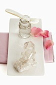 Bergkristall, Apothekerflasche und Blütenblätter