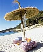 Badeutensilien und Getränke unter Sonnenschirm am Sandstrand