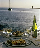 Two plates of food and wine on laid table by sea