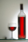 Glass and bottle of red wine (out of focus)