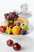 Dish of fruit, white cups and saucers in background