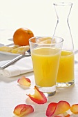 Orange juice in glass and carafe, orange in background