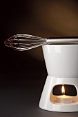 Chocolate sauce on food warmer with whisk
