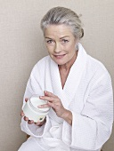 Mature woman in bathrobe with jar of cream