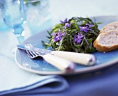 Rocket salad with borage flowers and baguette slices