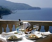 Fish dishes and wine on laid table with sea view