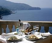 Gedeckter Tisch mit Fischgerichten und Wein am Meer