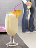 Pina colada on table, person in background