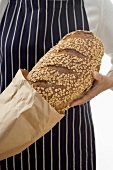 Woman putting a loaf of oat bread into a paper bag