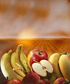Bananen, Äpfel und Getreide vor einem Getreidefeld
