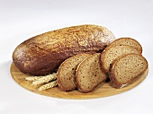 Whole loaf of brown bread with slices