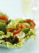 Mixed salad with lettuce and peppers on a glass platter