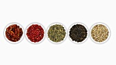 Four different types of peppercorns and dried chillies