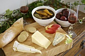 Cheese on a wooden board, pickled fruit and baguette