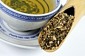 Patchouli herb in a wooden scoop with a cup of tea