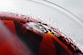 Red fruit juice with ice cubes in a glass